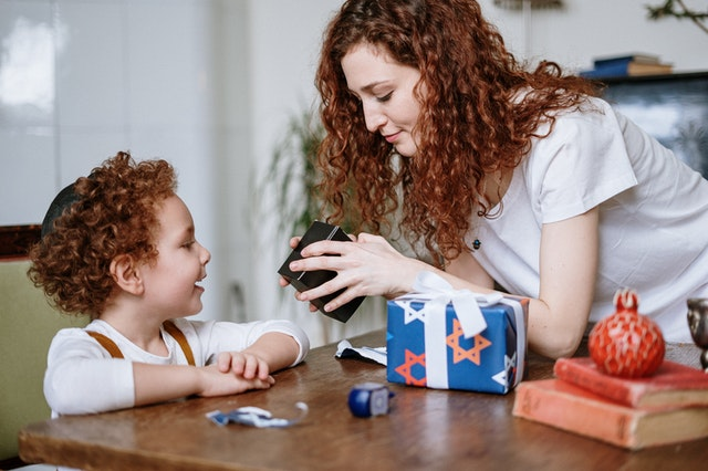 Mother showing a young child a toy